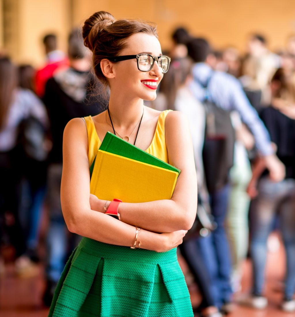 Portrait of a young female student dressed casually with colorful books during the break in crowded corridor at the old university
